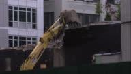 Construction excavator tears down part of brick wall in Williamsburg, Brooklyn.