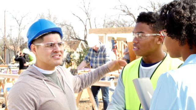 Construction foreman updates charity staff on progress of building home