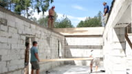 Construction of the roof. Builders lift the wooden beam to the roof.