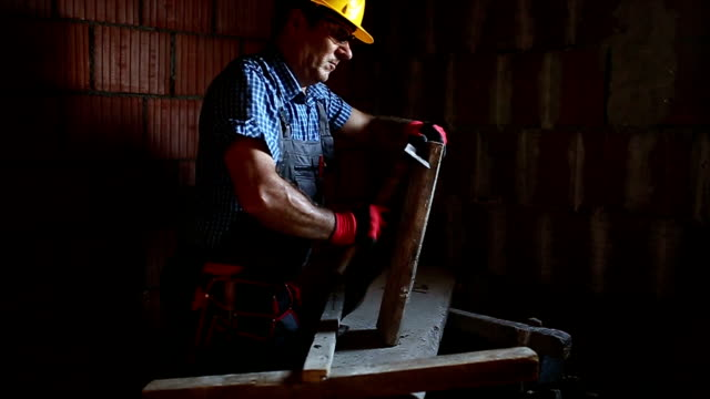 Construction roofer nailing wood board with hammer