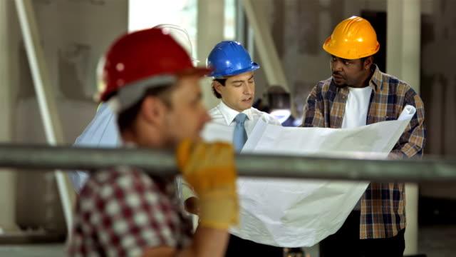 HD DOLLY: Construction Team Examining The Blueprints