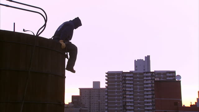 A construction worker dangles from the top of a construction site.