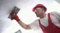 Construction worker finishing a ceiling.