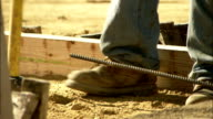 A construction worker hammers rebar into a beam. Available in HD.