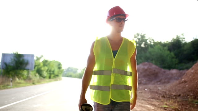 Construction worker holding megaphone,walking