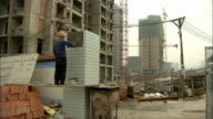 A construction worker lays tiles. Available in HD.