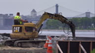 Construction worker rotates earth mover into parked position at construction site along East River.