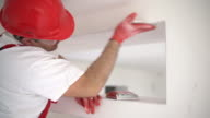 Construction worker sanding a drywall.