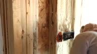 Construction Worker Spraying Expandable Foam Insulation Between Wall Studs