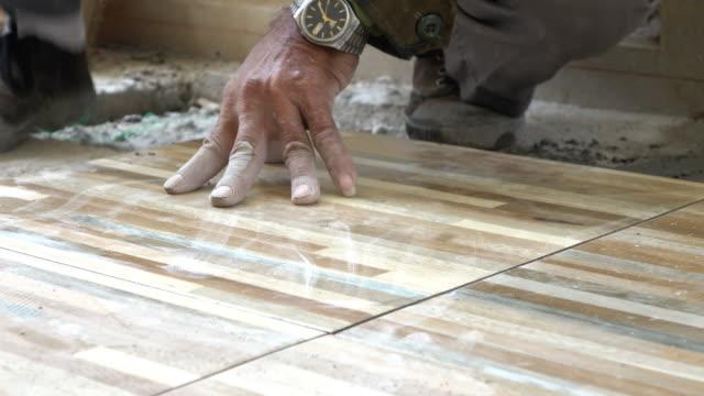 construction worker tiling ceramic tiles floor, dolly shot 4k