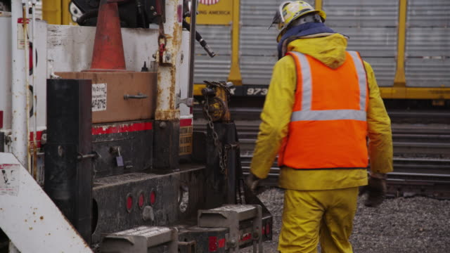 A construction worker unloads a heavy metal piece of industrial equipment from the back of a truck on a rainy day.