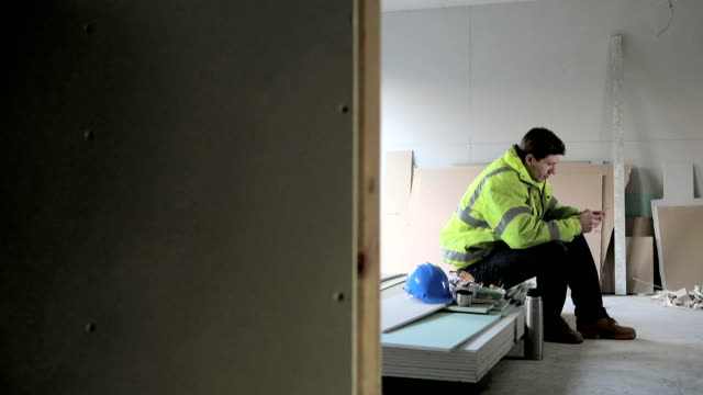 Bauarbeiter mit einem Mobiltelefon zu seiner Mittagspause