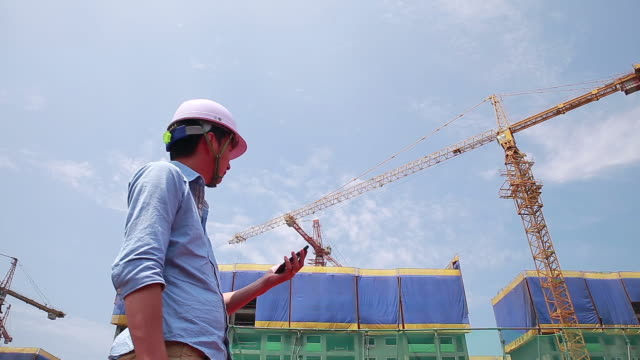 MS LA Construction worker using computer on mobile phone standing in front of cranes / Jeju, Jeju-do, South Korea