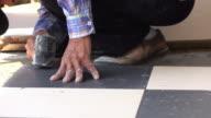 Construction worker using hammer tiling floor