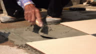 construction worker using putty knife tiling floor