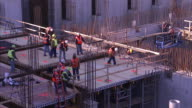 Construction workers build a high rise at a large construction site.