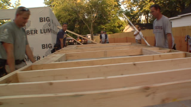 WS PAN Construction workers carrying frame of new house / Kalamazoo, Michigan, USA