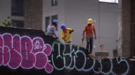 Construction workers chip away at graffiti painted brick wall on rooftop in Brooklyn.