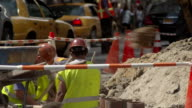 Construction workers dig a hole on a busy Manhattan Street.  People and traffic bustle around them.