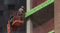 Construction workers drill into building exterior atop high rise lift in Brooklyn, New York.