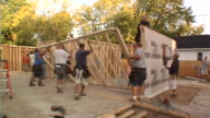 WS Construction workers lifting frame of new house and positioning it / Kalamazoo, Michigan, USA