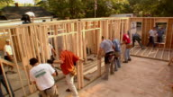 HA WS Construction workers lifting frame of new house and positioning it / Kalamazoo, Michigan, USA