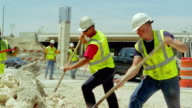 MS, PAN, construction workers moving rubble with spades on construction site, San Antonio, Texas, USA