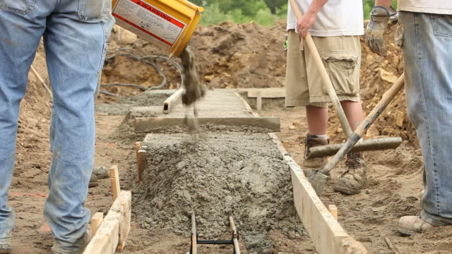 Construction Workers Pouring Concrete Footings