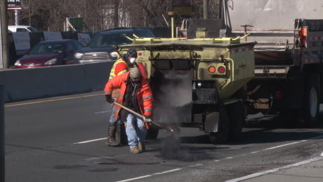 Construction workers rush to repair large potholes that have formed on Route 4 near the George Washington Bridge as a result of drastically changing...