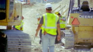 MS, construction workers shifting rubble with spades on construction site, San Antonio, Texas, USA