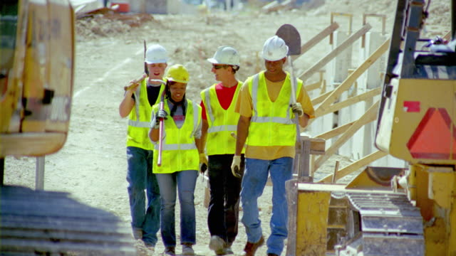 MS, construction workers walking on building site, San Antonio, Texas, USA
