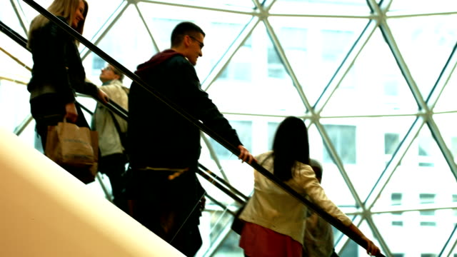 Consumers Riding Down The Escalator Side View
