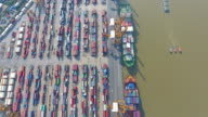 4K : Container Cargo freight ship with working crane bridge in shipyard