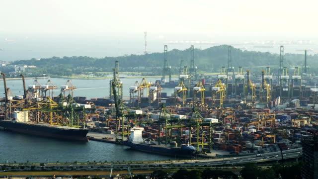 Container Cargo Fracht versenden mit Kran Laden arbeiten Brücke in der Werft in der Dämmerung für Logistik Import Export Hintergrund