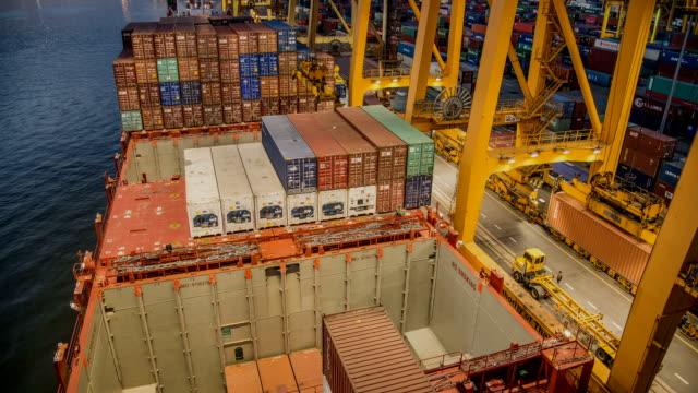 Timelaps des Container Fracht Fracht versenden mit Kran Laden arbeiten Brücke in der Werft in der Dämmerung für Logistik Import Export Hintergrund Ansicht von Schiff