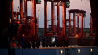 MS Container carriers in container terminal at dusk, Hamburg, Germany
