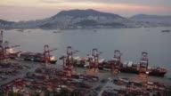 HA, MS Container ships being unloaded at sunset at Busan Port and view across harbour and city / Busan, South Korea
