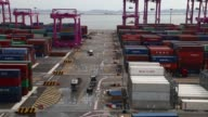 Container trucks move past stacked shipping containers at the Sun Kwang Newport Container Terminal in Incheon New Port in Incheon South Korea on...