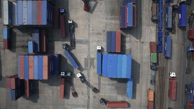 Containers sit stacked as trucks drive past in an aerial view directly overhead taken above the Uiwang Inland Container Depot in Uiwang South Korea...