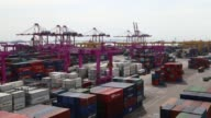 Containers sit stacked beneath gantry cranes at the Sun Kwang Newport Container Terminal in Incheon New Port in Incheon South Korea on Monday Sept 4...