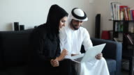 Content Middle Eastern Couple Viewing Photos and Videos on Laptop