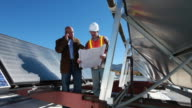 WS PAN Contractor and architect looking at blueprints on roof top with solar hot water heaters / Santa Fe, New Mexico, USA