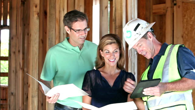 Contractor building home, talking with couple