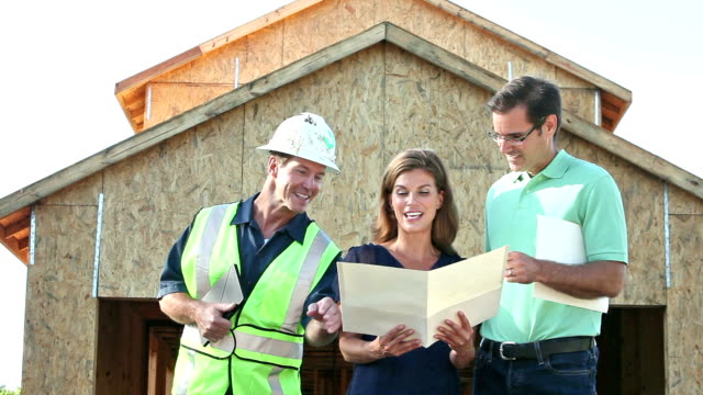 Contractor building home, with couple looking at plans