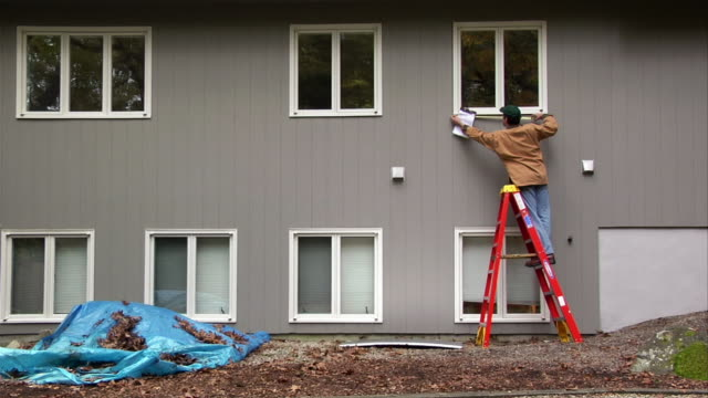 Contractor on ladder outside house measuring window / recording measurement on clipboard