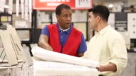 Contractor shopping for building materials in home improvement store with salesman