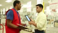 Contractor with house plans on digital tablet shopping