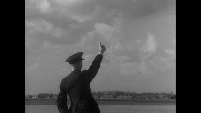 B/W Control tower giving hand signal to ground crewman, who passes it to pilot of cargo biplane, and biplane taxiing for takeoff / Croydon, England, United Kingdom