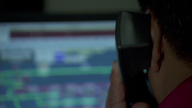 A controller speaks on a telephone as he monitors railroad statuses on a computer screen.