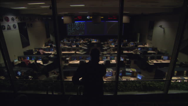 WS Controller talking on phone and looking through window at mission control room, Houston, Texas, USA